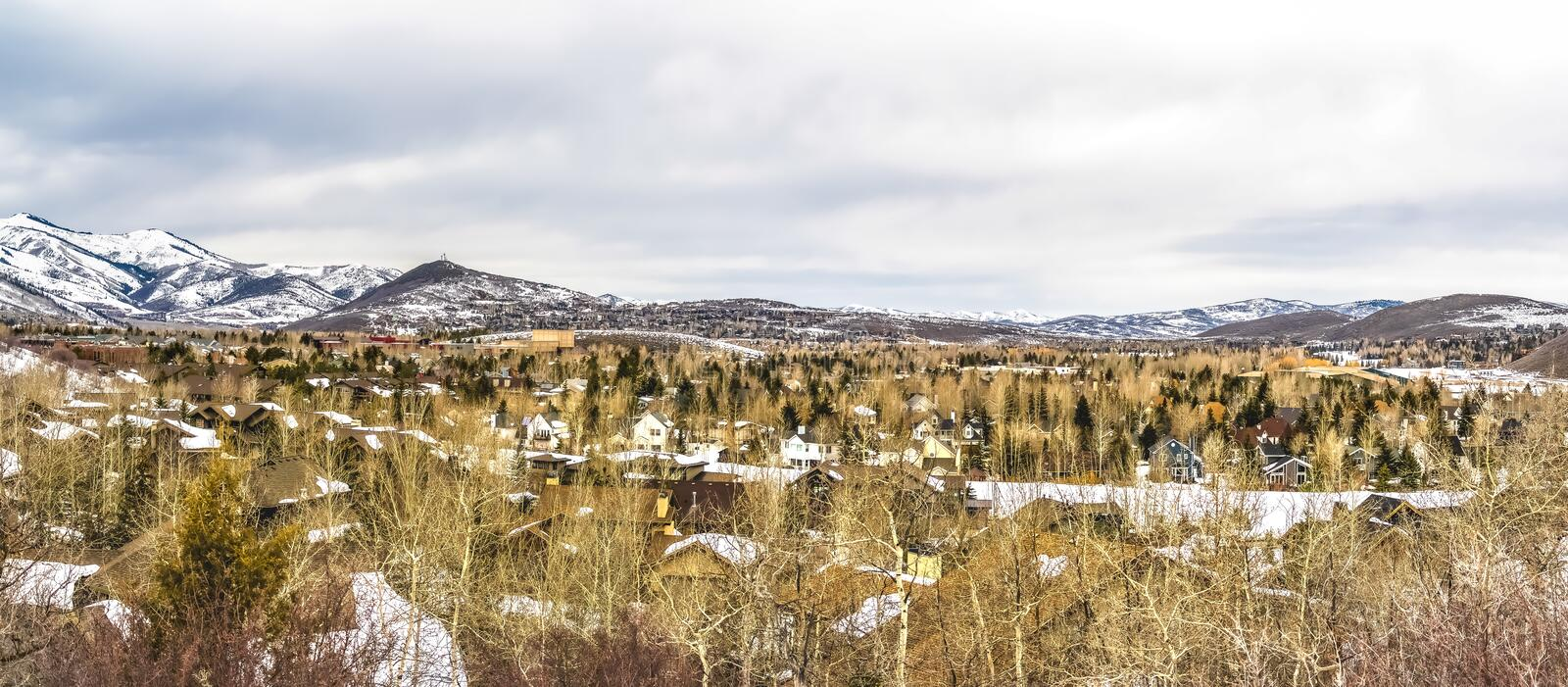 Panoramic view of houses and majestic mountain against cloudy sky in winter. Conifers and trees with leafless branches grows around the residential area royalty free stock image