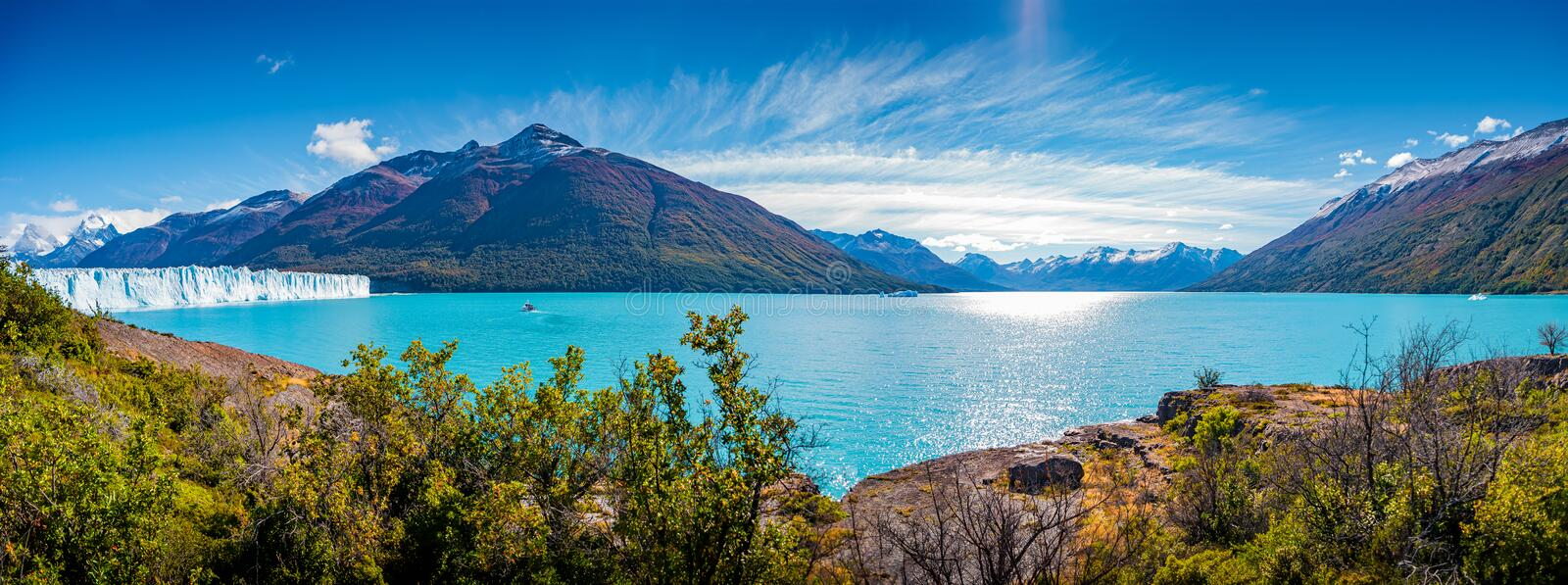 Panoramic view of the huge Perito Moreno glacier in Patagonia in golden Autumn, South America, sunny day, blue sky royalty free stock photos