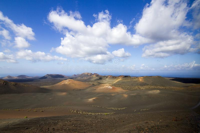 Panoramic view of Lanzarote volcanic island with blue cloudy sky. Travel nature tourism spain desert volcano canary landscape mountain lava rock beautiful royalty free stock images