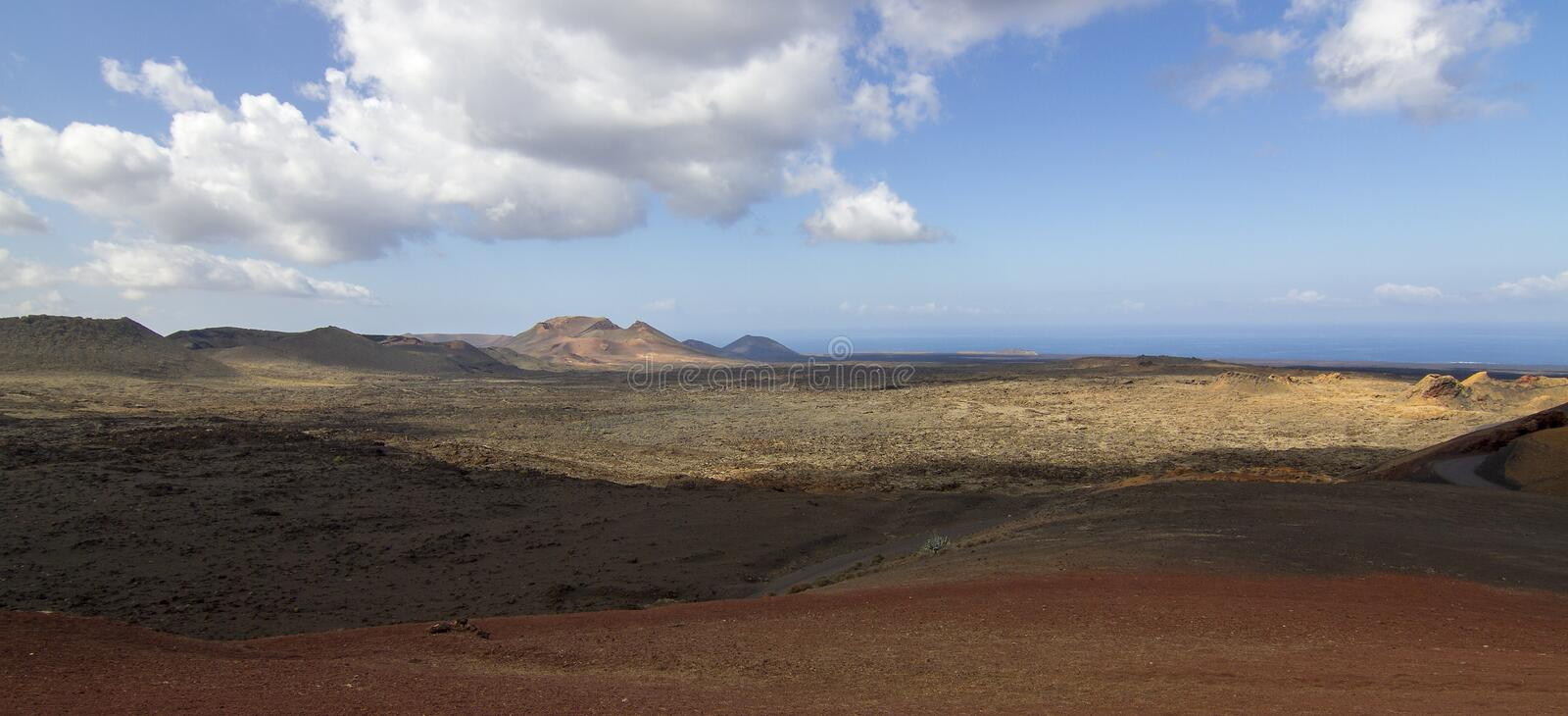 Panoramic view of Lanzarote volcanic island with blue cloudy sky. Travel nature tourism spain desert volcano canary landscape mountain lava rock beautiful royalty free stock image