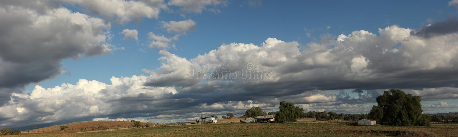 Panoramic view of large open dry drought affected farm fields under stretching cloud filled blue skies with farm buildings in. Rural New South Wales, Australia royalty free stock photo