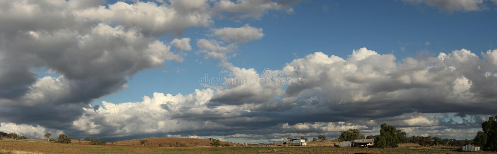 Panoramic view of large open dry drought affected farm fields under stretching cloud filled blue skies with farm buildings in. Rural New South Wales, Australia stock photography
