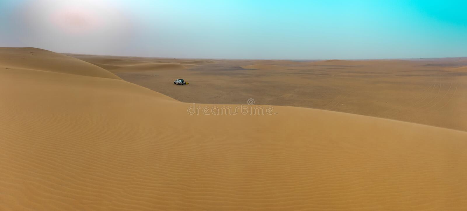 Panoramic view from a large sand dune in the northern desert of Sudan over the desert landscape with the rising sun and an. Overnight camp in the background stock photography