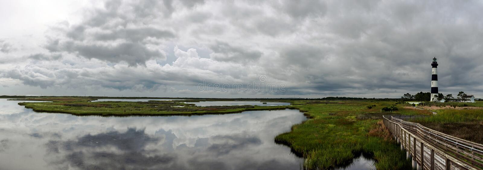 Panoramic view of lighthouse and surrounding marshlands. A panoramic shot of the Bodie Island Lighthouse and surrounding wetland marshes and the clouds royalty free stock photography