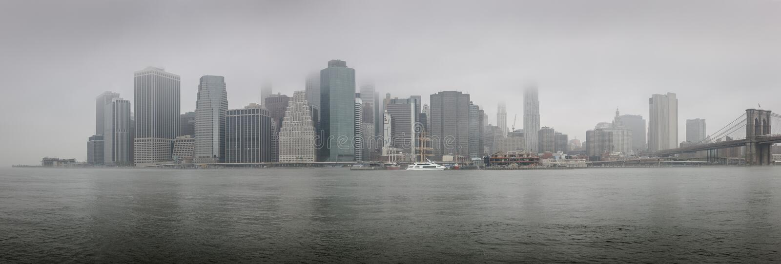 Panoramic view of Lower Manhattan on a foggy morning - NYC. Foggy morning in New York City: panoramic view of East River, Lower Manhattan and the Financial royalty free stock image