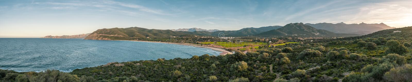 Panoramic view of Lozari beach and distant mountains in Corsica royalty free stock image