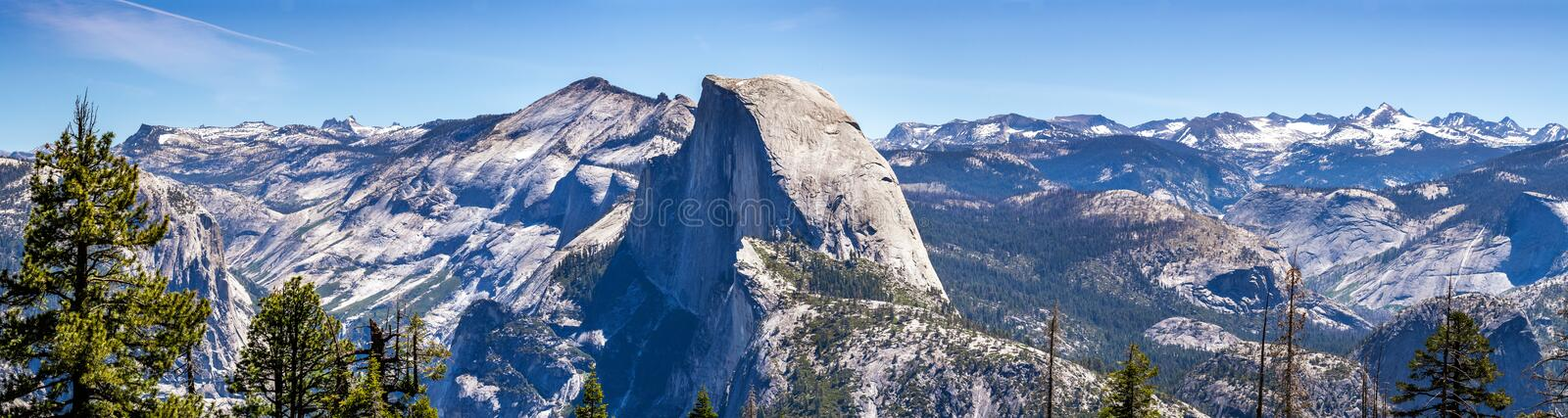 Panoramic view of the majestic Half Dome and the surrounding wilderness area with mountain peaks and ridges still covered by snow. Yosemite National Park stock image