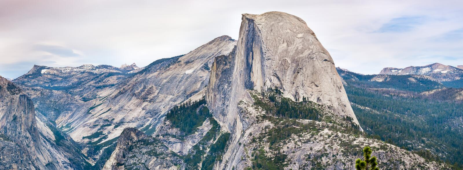 Panoramic view of the majestic Half Dome and the surrounding wilderness area with mountain peaks and ridges still covered by snow. Yosemite National Park stock photography