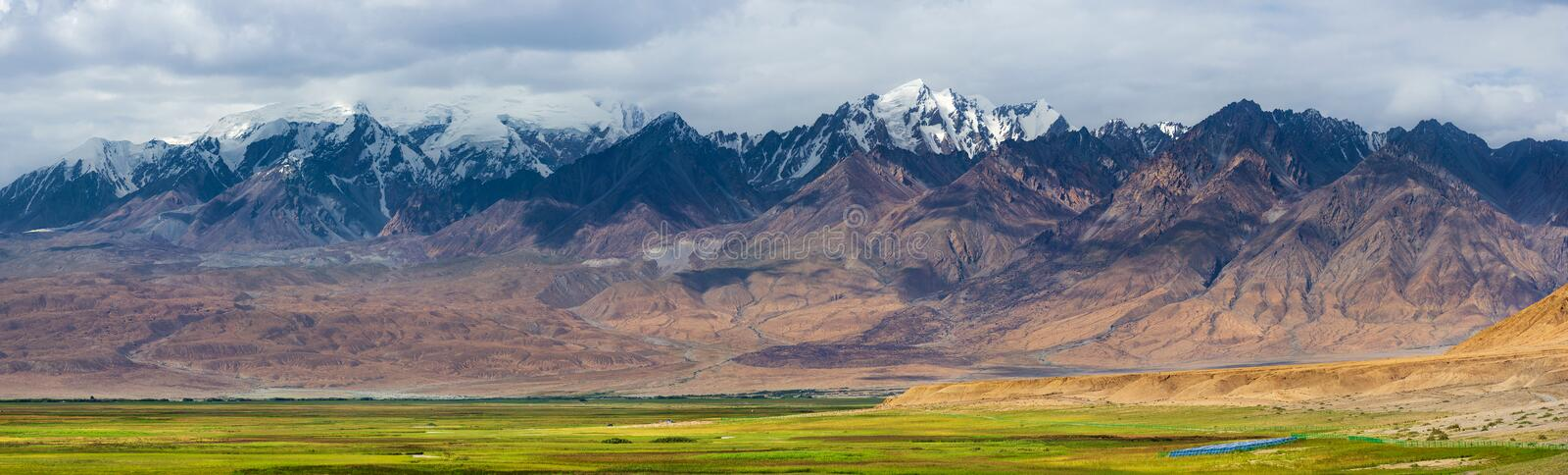 Panoramic landscape of snow-capped mountain ranges with fresh green meadows of prairie royalty free stock photography