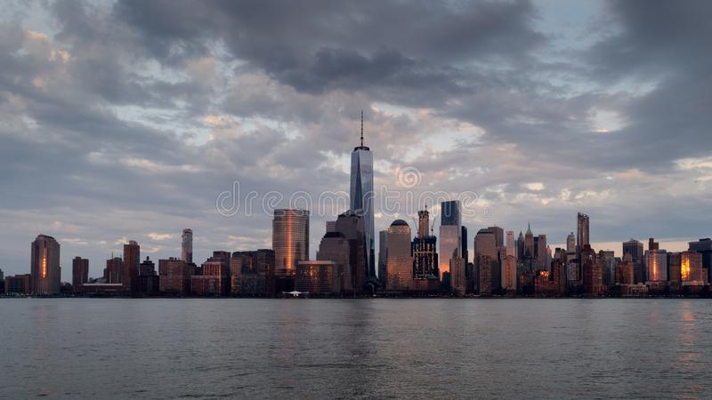 Panoramic view of Manhattan skyline with its reflection in Hudson river at dusk from New Jersey pier. New York, USA royalty free stock photo