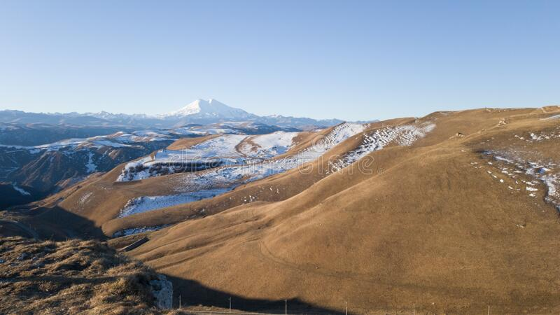 Panoramic view of mount Elbrus. Autumn trip to the Caucasus. Yellow dry field. Trip to Russia in winter royalty free stock photo