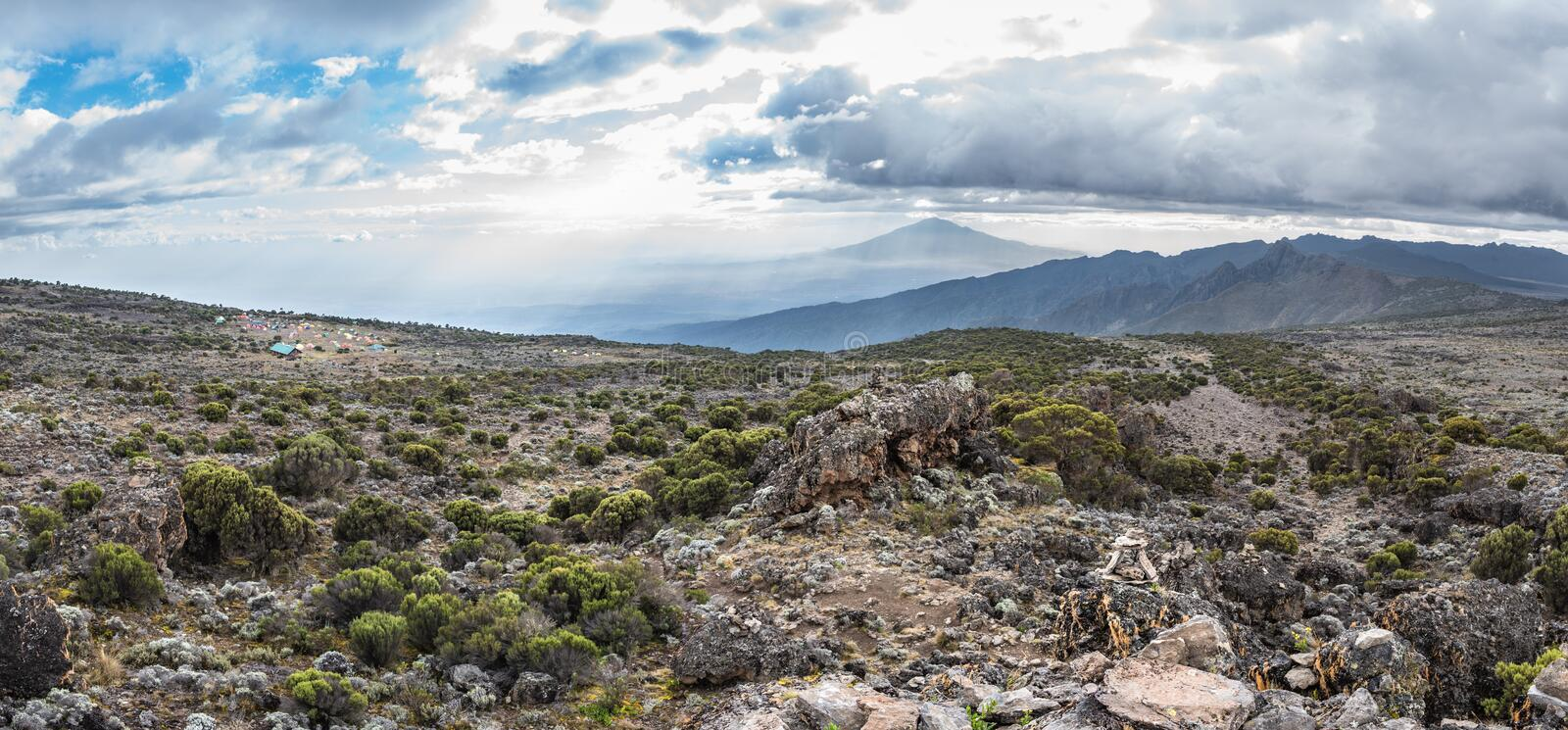 Panoramic view of Mount Meru and the Shira Cave Camp site on the Machame hiking route on Mt Kilimanjaro, Tanzania. Panoramic view of the Shira Cave Camp site on stock images