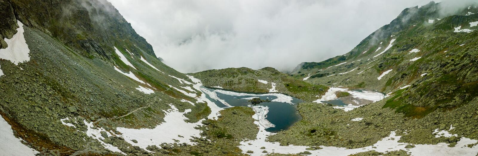 Panoramic view of mountain lake and snow surrounding it.  stock images