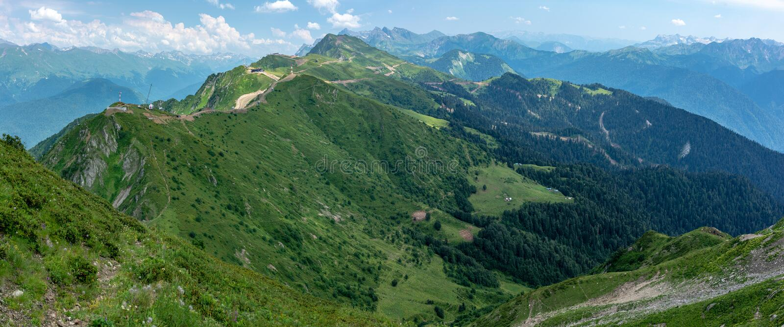 Panoramic view of the mountain range with cable cars and Green Valley. Caucasus, Russia royalty free stock photo