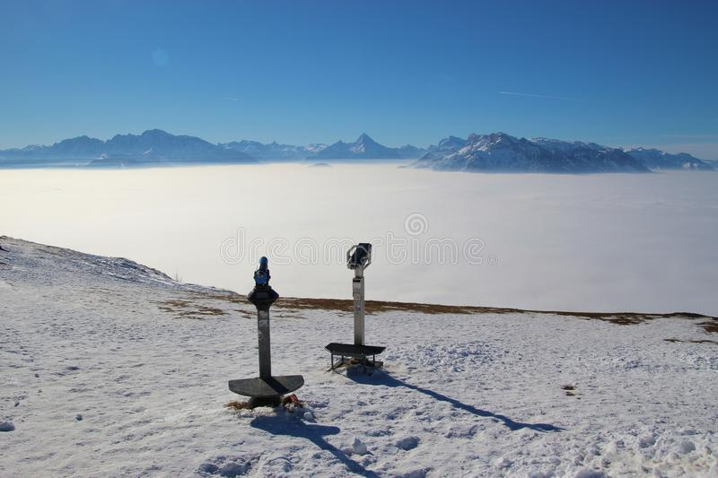 Panoramic view of mountain summits over high fog. stock photos
