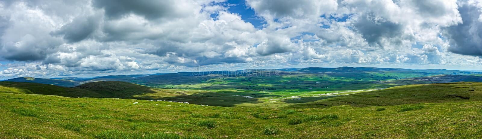 A panoramic view of a mountain valley with grassy green slope under a majestic blue sky and white clouds stock photo