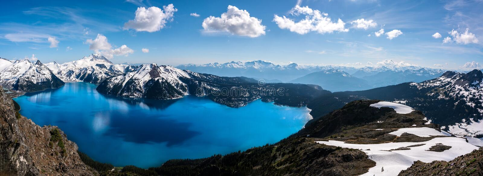 Panoramic view of mountains and turquoise coloured lake in Garibaldi provincial park, BC, Canada. Snow mountains and blue sky royalty free stock images