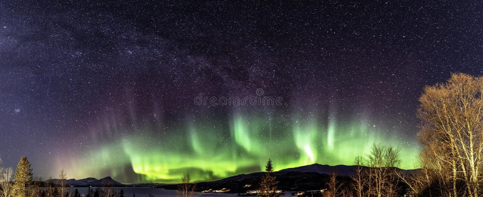 Panoramic view of multicolored strong lighting Aurora curved above Scandinavian mountains and frozen lake, very cold winter night. Deep clear sky, Rossvatnet stock image