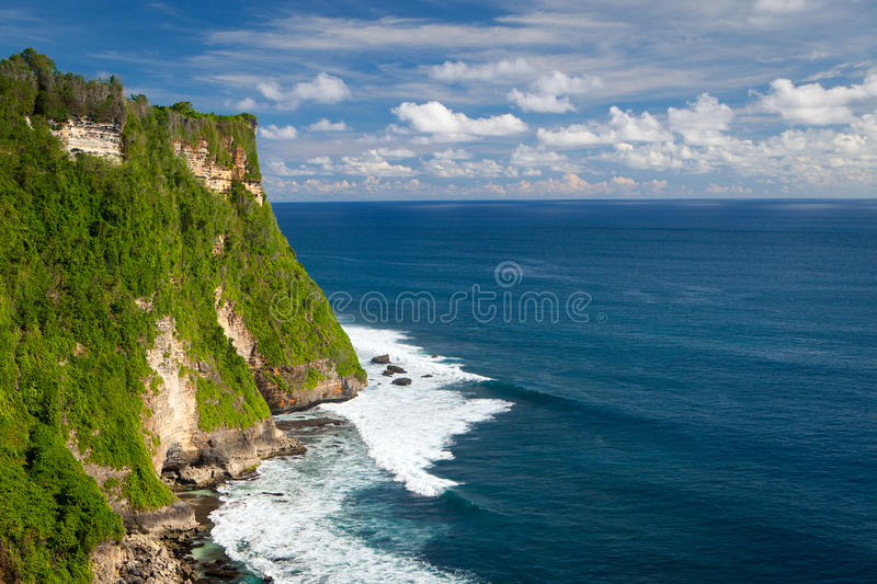 Panoramic view of the ocean with waves high cliff. Panoramic view of the ocean with waves with a high cliff on a Sunny day with clouds. Uluwatu, Bali stock photos