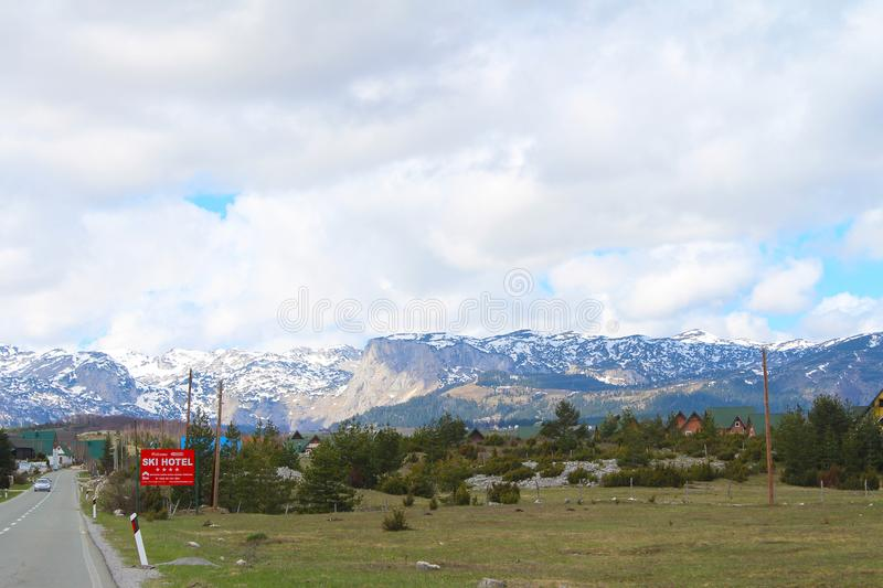 Panoramic view with old rural houses from the beautiful green plateau of Zabljak mountain to the snowy Durmitor mountain royalty free stock photos