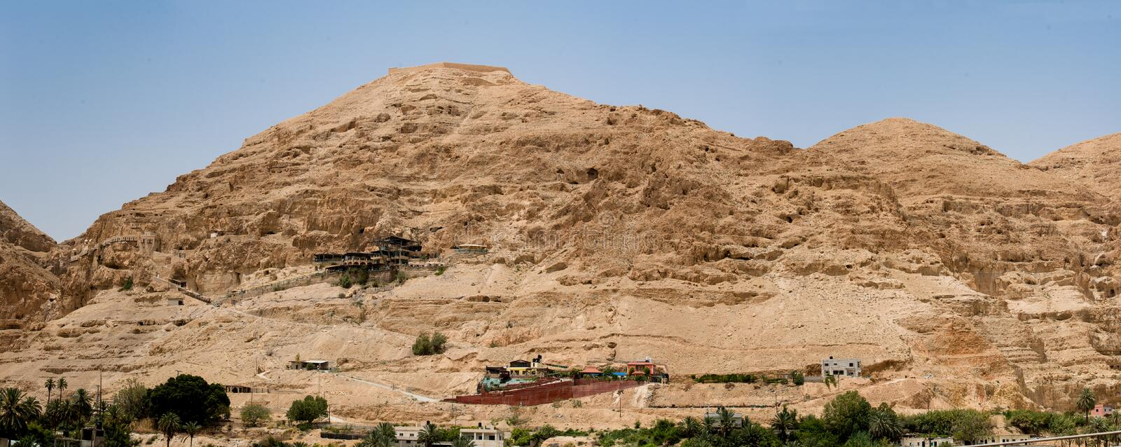 Mount of Temptation in the desert with acable car and the Monastery of Qurantul stock photography