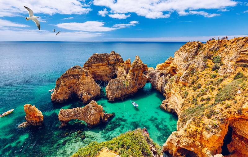 Panoramic view, Ponta da Piedade with seagulls flying over rocks near Lagos in Algarve, Portugal. Cliff rocks, seagulls and. Tourist boat on sea at Ponta da royalty free stock photo