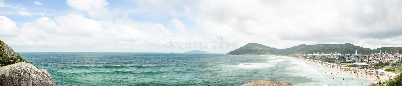 Panoramic view of Praia Brava beach in Florianopolis, Brazil. The sea, some stones, mountains and people on the beach stock image