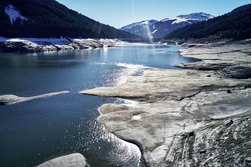 Panoramic view of a reservoir lake at winter with cracked mud around. Water in the high alps in austria by day with stock image