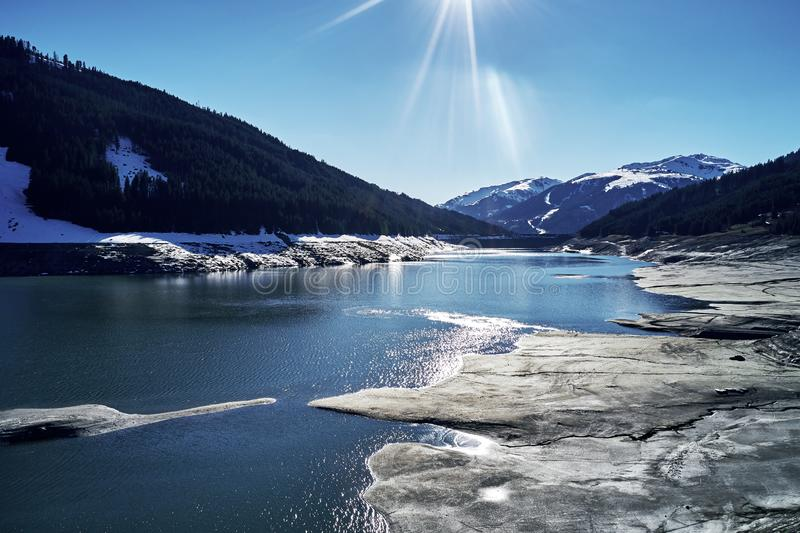 Panoramic view of a reservoir lake at winter with cracked mud around. Water in the high alps in austria by day with royalty free stock image