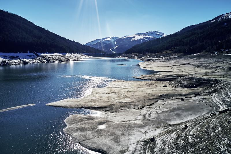 Panoramic view of a reservoir lake at winter with cracked mud around. Water in the high alps in austria by day with royalty free stock photos