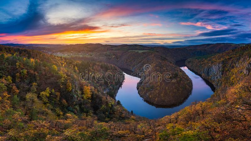 Panoramic view of river canyon with dark water and autumn colorful forest. Horseshoe bend, Vltava river, Czech republic. Beautiful landscape with river. Maj stock photography
