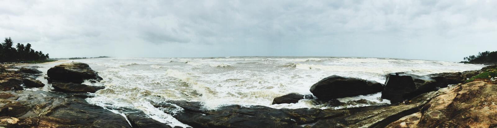 Panoramic view of the rocky beaches of Kundapura. Rocky beaches and the violent sea waves at Kundapura royalty free stock photos