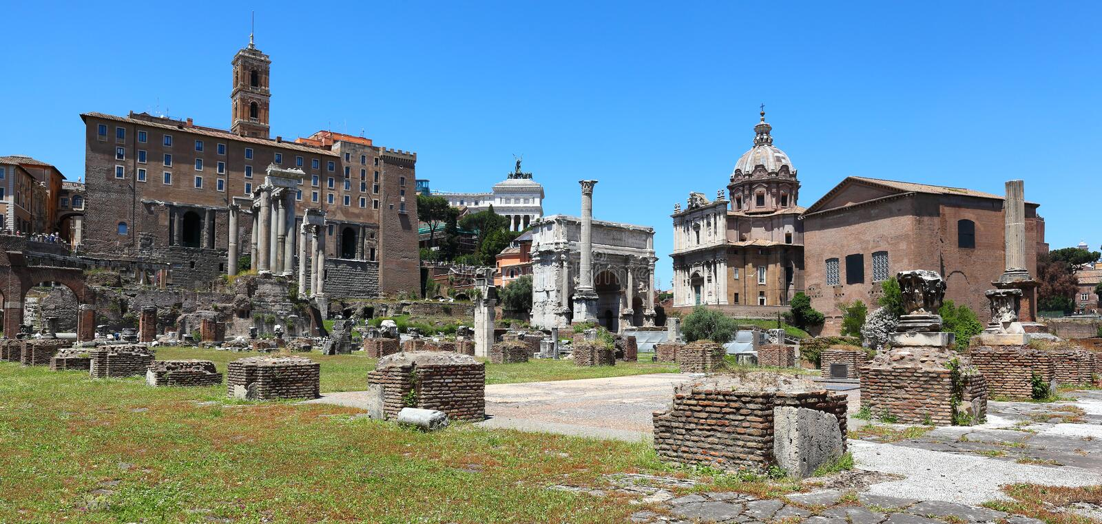 The ancient Forum, Rome - Italy. Panoramic view of the Roman Forum looking towards the Remains of the Temple of Saturn, the Arch of Septimus Severus, and the stock photography