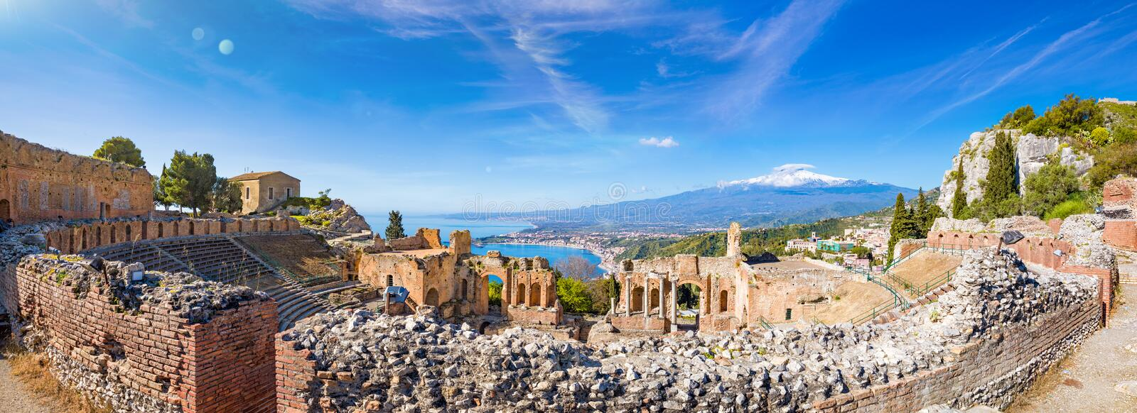 Panoramic view of ruins of Ancient Greek theatre in Taormina on background of Etna Volcano, Italy stock images