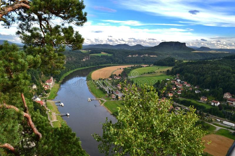 Panoramic view of Saxon Switzerland from the summits of Bastei Park. The river Elbe, berth, ferries, town of Bad Schandau, greenery and hills royalty free stock photography