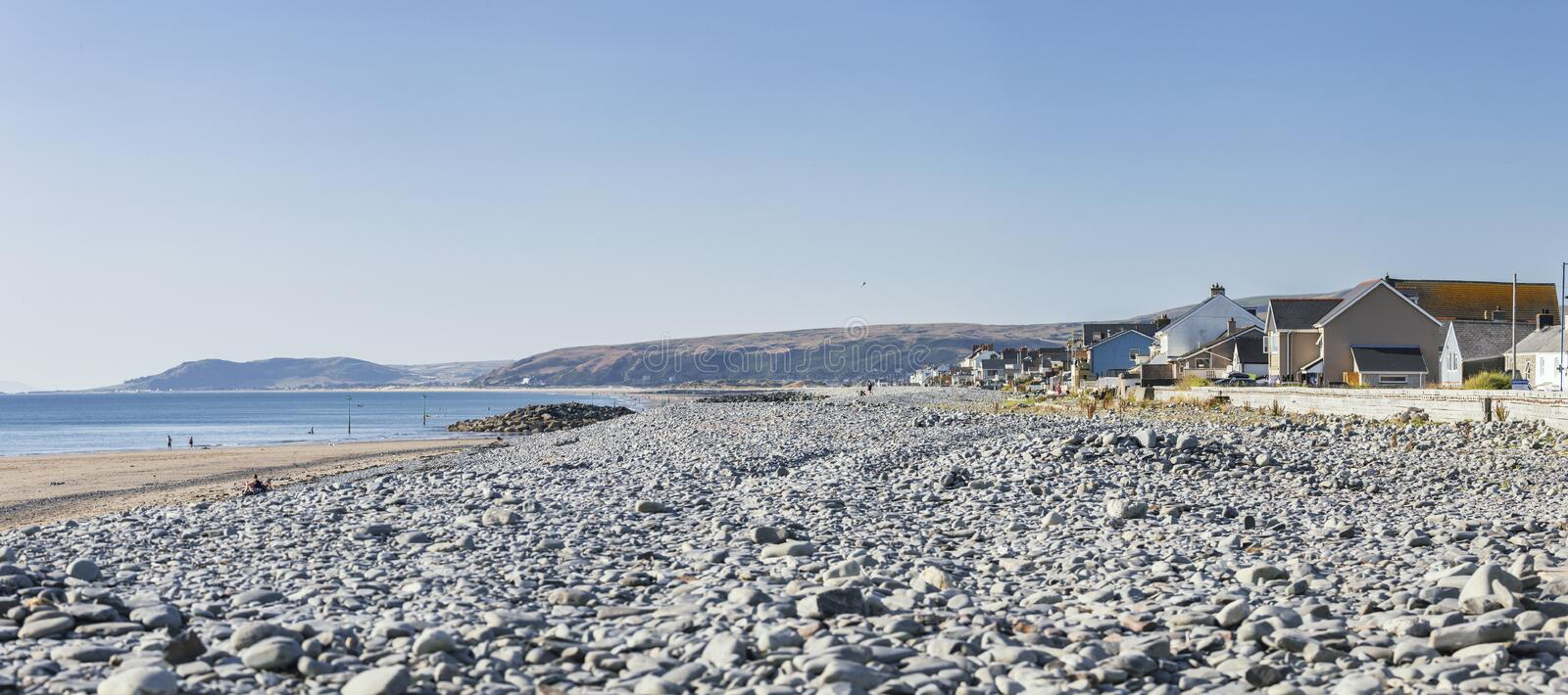Panoramic View of Scenic Beach in Wales, UK. Panoramic view over scenic pebble beach at low tide on bright summer day in Borth, Wales in United Kingdom stock photo