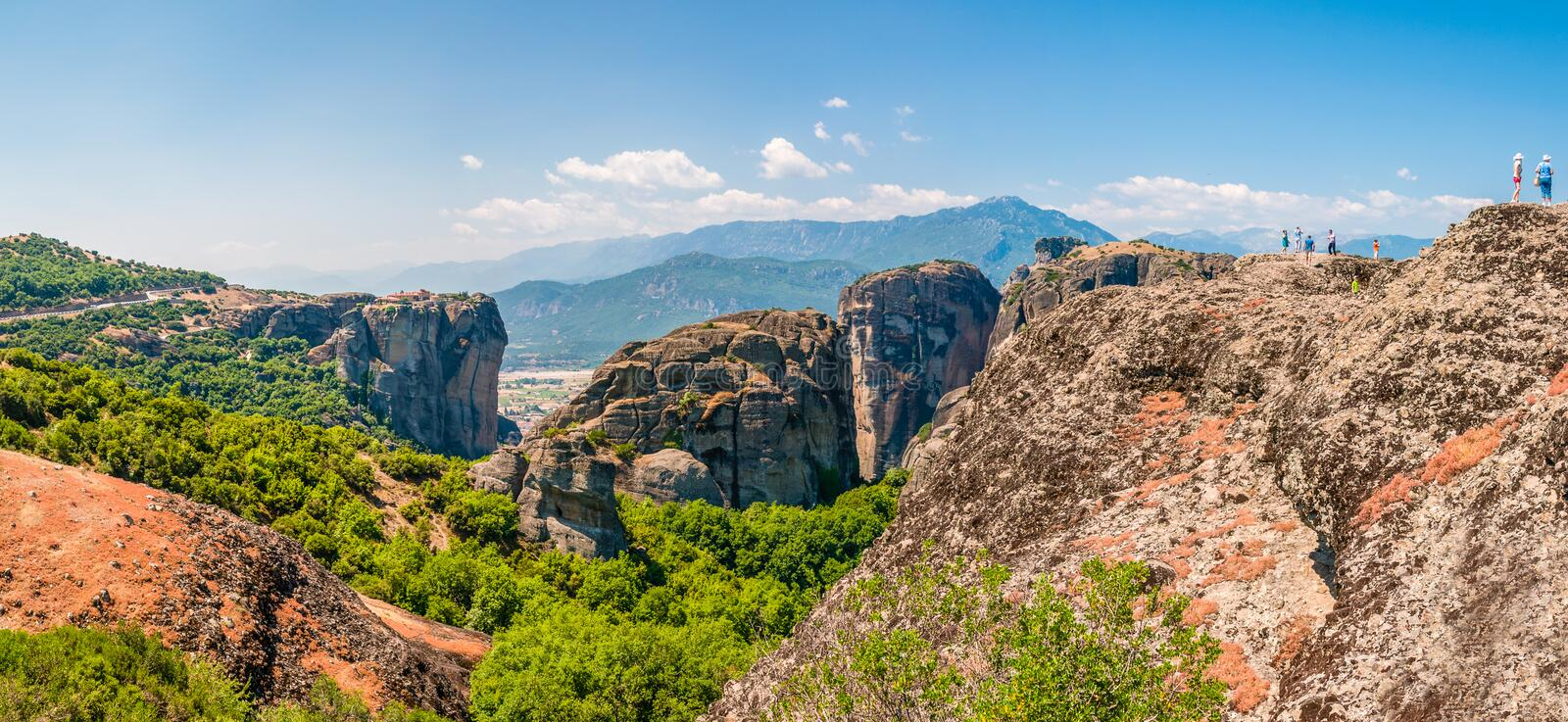 Panoramic view on scenic Meteora landscape rock formations with monasteries on one of the cliffs and traveling people on another. royalty free stock images