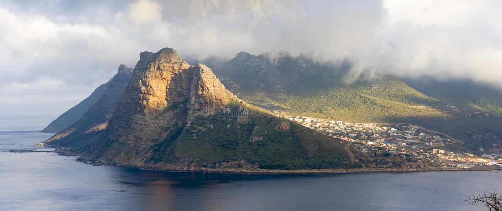 Panoramic view of the Sentinel rock guarding Hout Bay harbor on the Cape Peninsula near to Cape Town in South Africa. The view is stock image