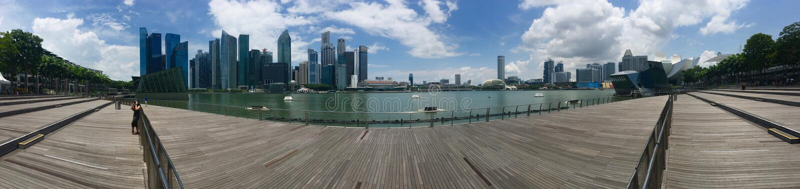 Panoramic view of Singapore Marina Band Sands area. Wooden plank platform overlooking the bay, green trees on both sides and skyscraper on a sunny blue sky day royalty free stock photos