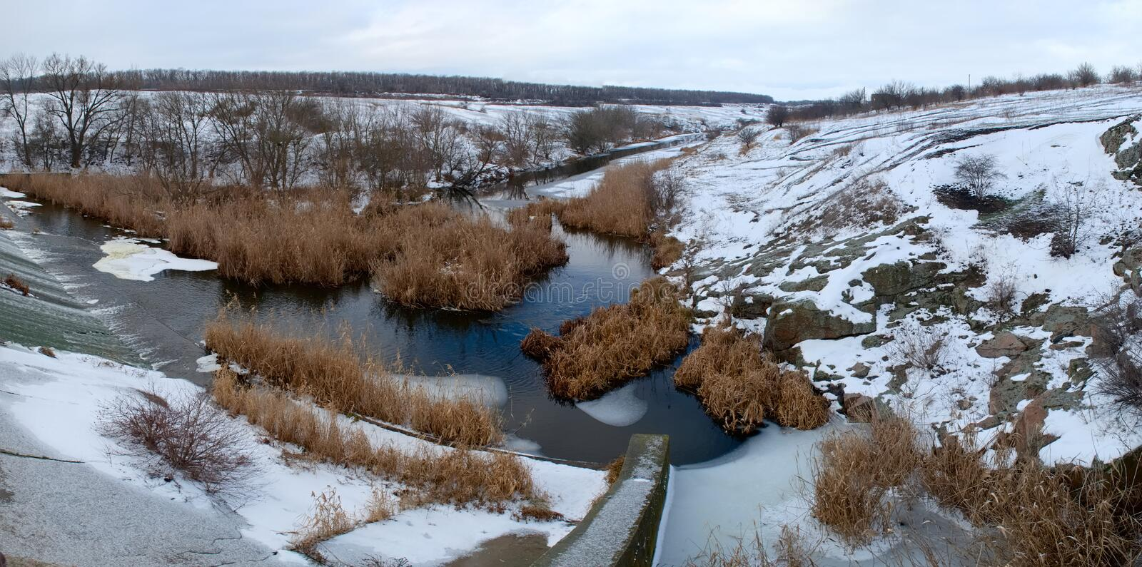 Panoramic view of small dam on the river in winter. Panoramic view of small concrete dam on the river in winter stock photos