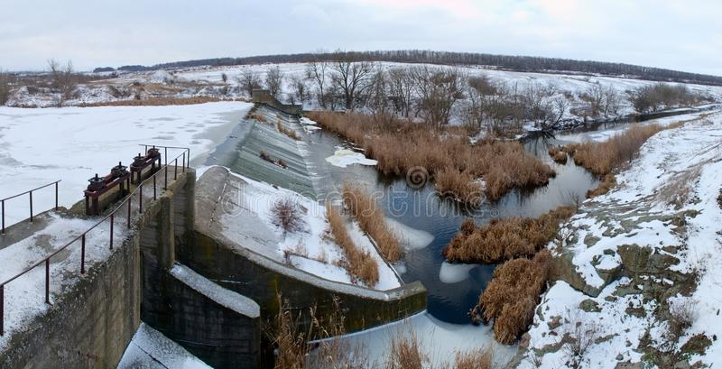 Panoramic view of small dam on the river in winter. Panoramic view of small concrete dam on the river in winter royalty free stock photo