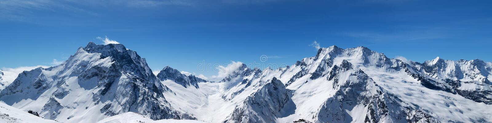 Panoramic view of snow-capped mountain peaks royalty free stock image
