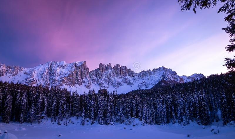 Panoramic view of snow covered lake carezza lago di carezza, karersee and latemar in winter; unesco world heritage, dolomites. Italy stock image