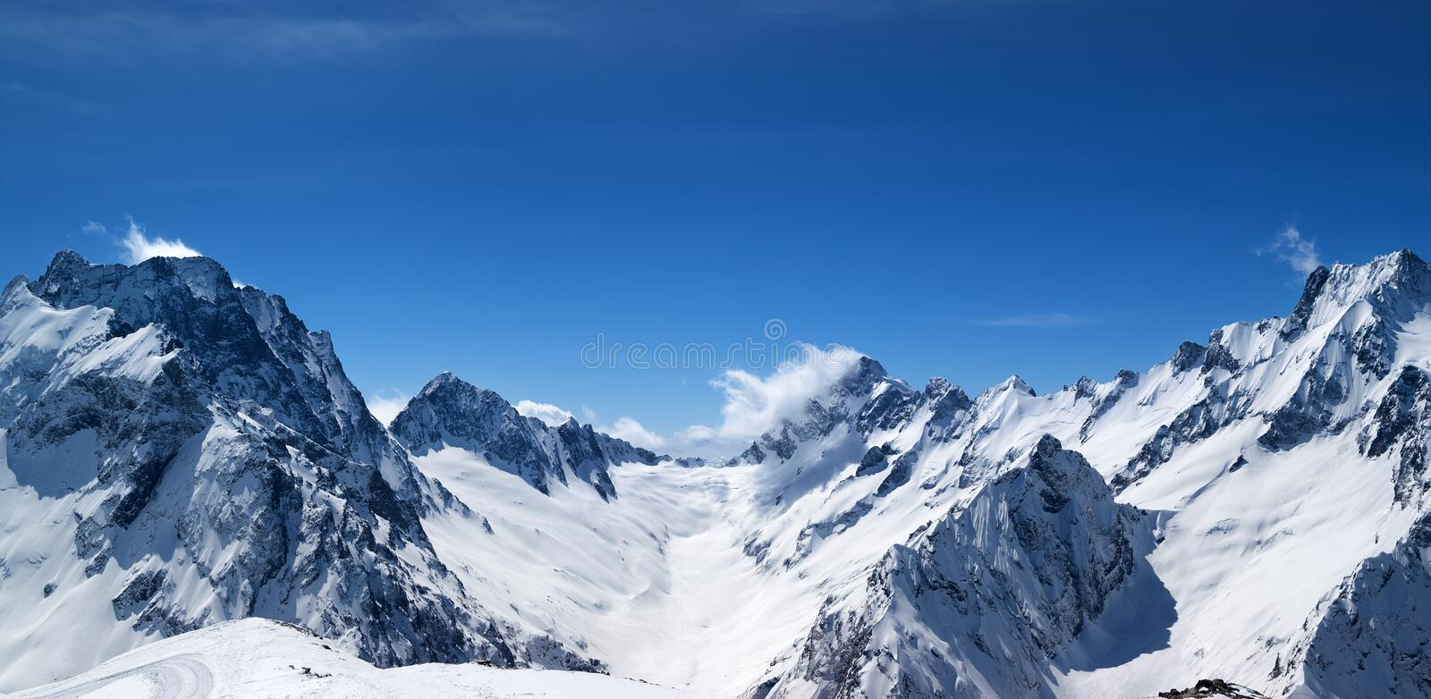 Panoramic view of snow covered mountain peaks. With mount Dombay-Ulgen and beautiful blue sky with clouds at sun windy day. Caucasus Mountains in winter, region stock photos