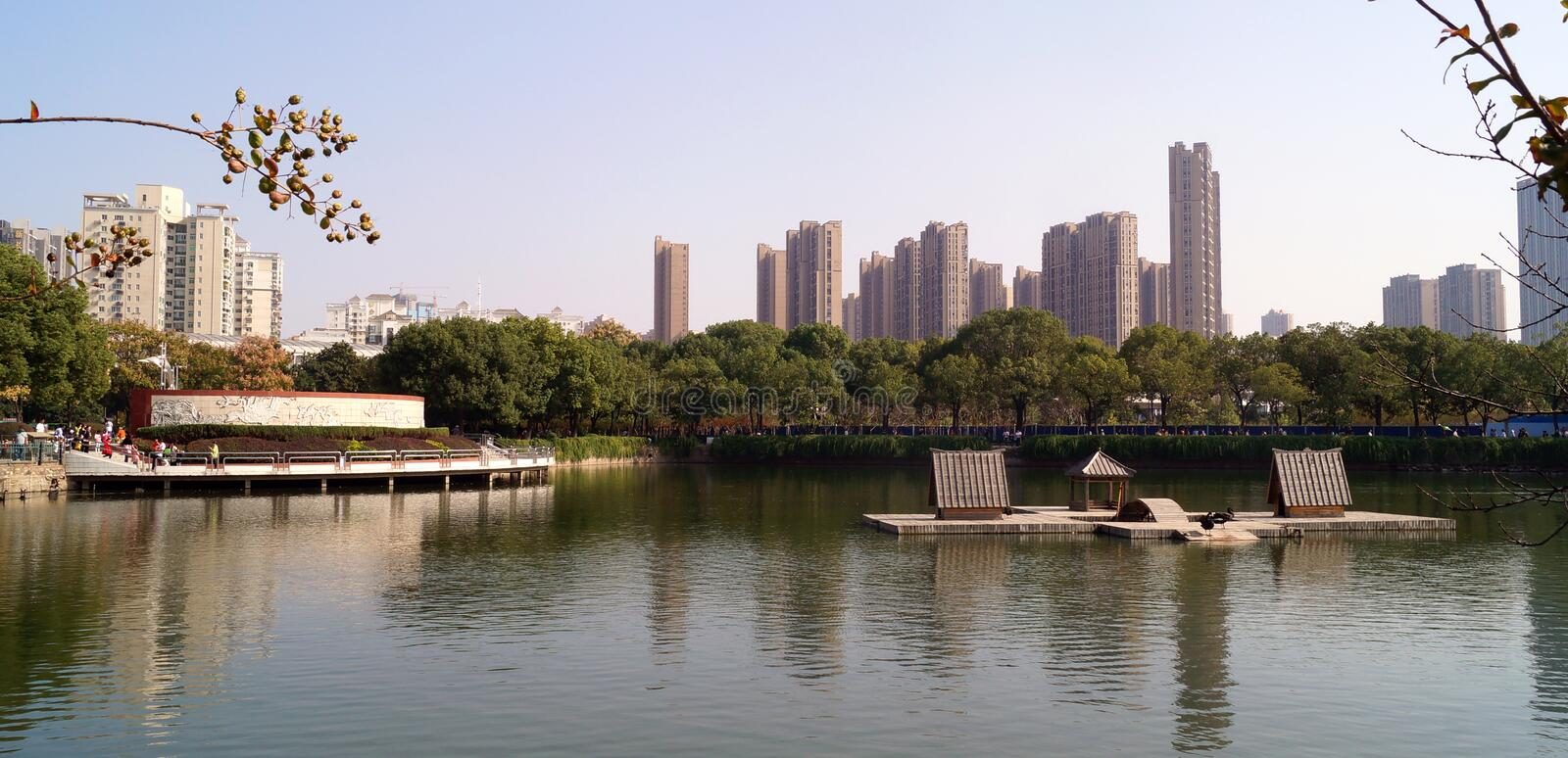 Wuhan zoo China. Panoramic view of some part of wuhan city, view from the zoo, green trees in a park side to tall buildings a small lake and and some houses royalty free stock image