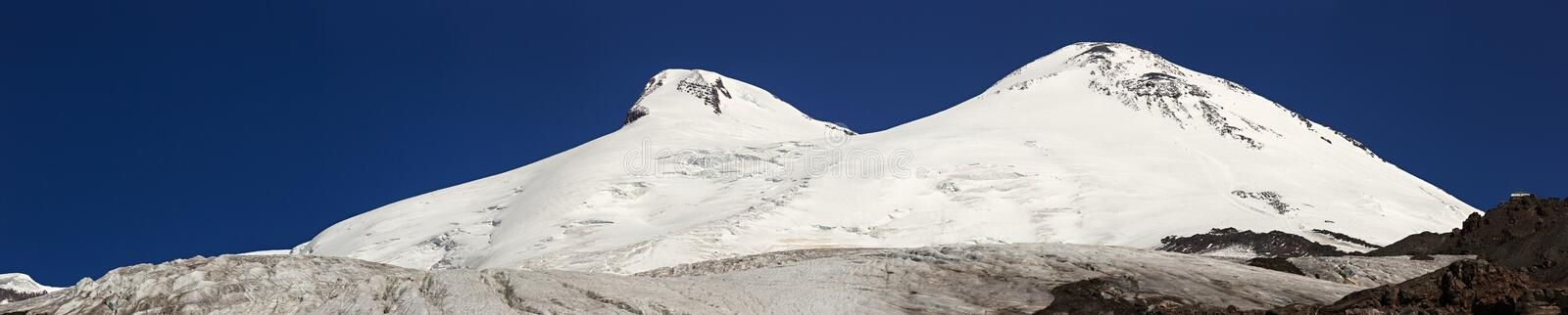 Panoramic view of the southern slope of Mount Elbrus. Of the Caucasus Mountains in Russia. Snow-covered mountain peaks with two peaks royalty free stock image