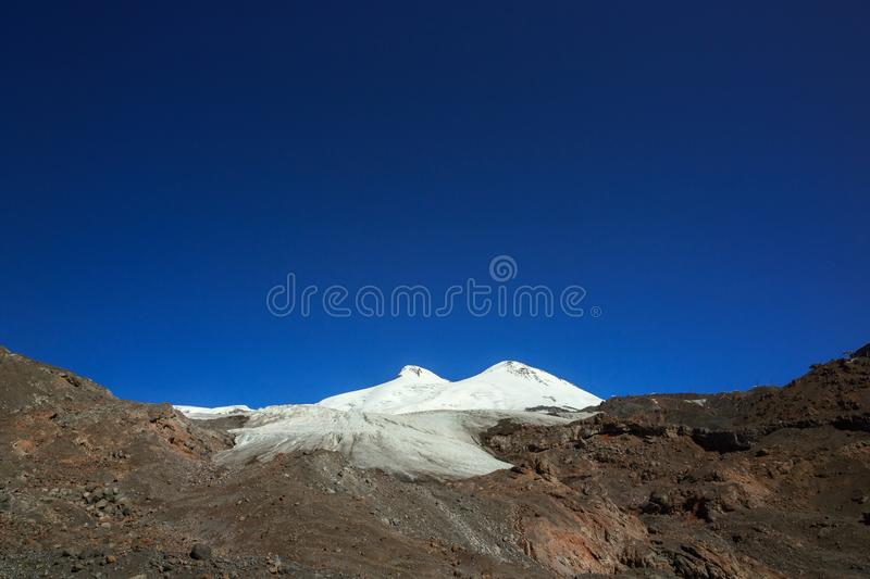 Panoramic view of the southern slope of Mount Elbrus. Of the Caucasus Mountains in Russia. Snow-covered mountain peaks with two peaks royalty free stock photos