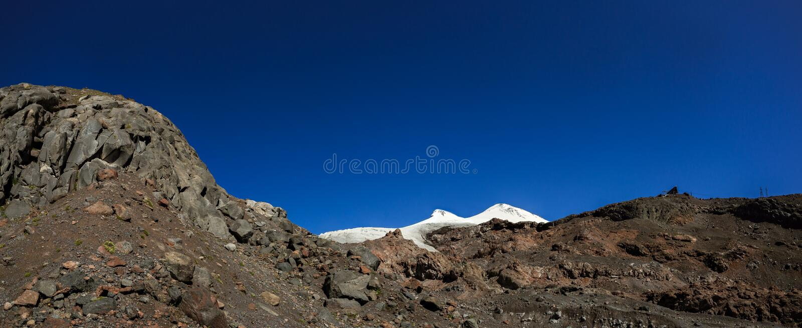 Panoramic view of the southern slope of Mount Elbrus. Of the Caucasus Mountains in Russia. Snow-covered mountain peaks with two peaks royalty free stock images