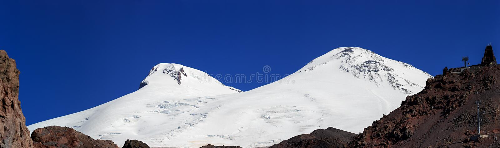 Panoramic view of the southern slope of Mount Elbrus. Of the Caucasus Mountains in Russia. Snow-covered mountain peaks with two peaks stock photo