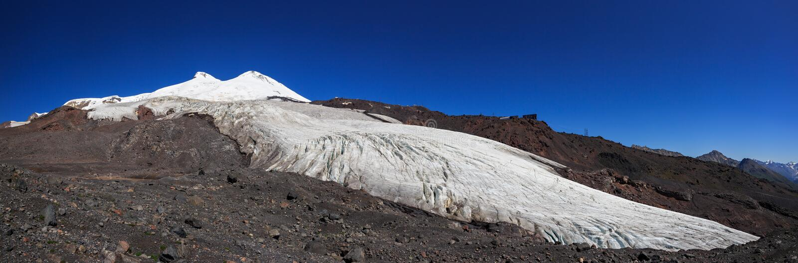 Panoramic view of the southern slope of Mount Elbrus. And the Small Azau Glacier of the Caucasus Mountains in Russia. Snow-covered mountain two peaks royalty free stock image